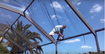 A screen repairman sits atop a screened lanai replacing material.